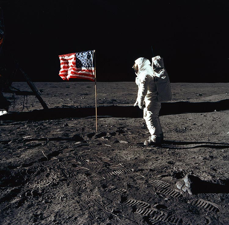Astronaut Edwin E. Aldrin Jr., lunar module pilot of the first lunar landing mission, poses for a photograph beside the deployed United States flag during an Apollo 11 extravehicular activity (EVA) on the lunar surface. The Lunar Module (LM) is on the left, and the footprints of the astronauts are clearly visible in the soil of the moon. Astronaut Neil A. Armstrong, commander, took this picture with a 70mm Hasselblad lunar surface camera. Image Credit: NASA