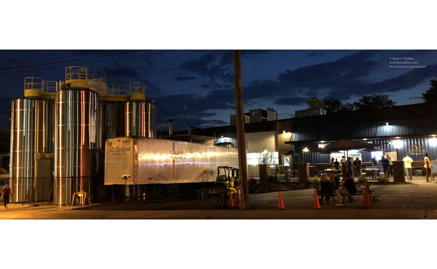 The Catawba Brewing Company tanks reflect light at night in Downtown Morganton with the tap room drawing a crowd for bands. ©Mark D Phillips