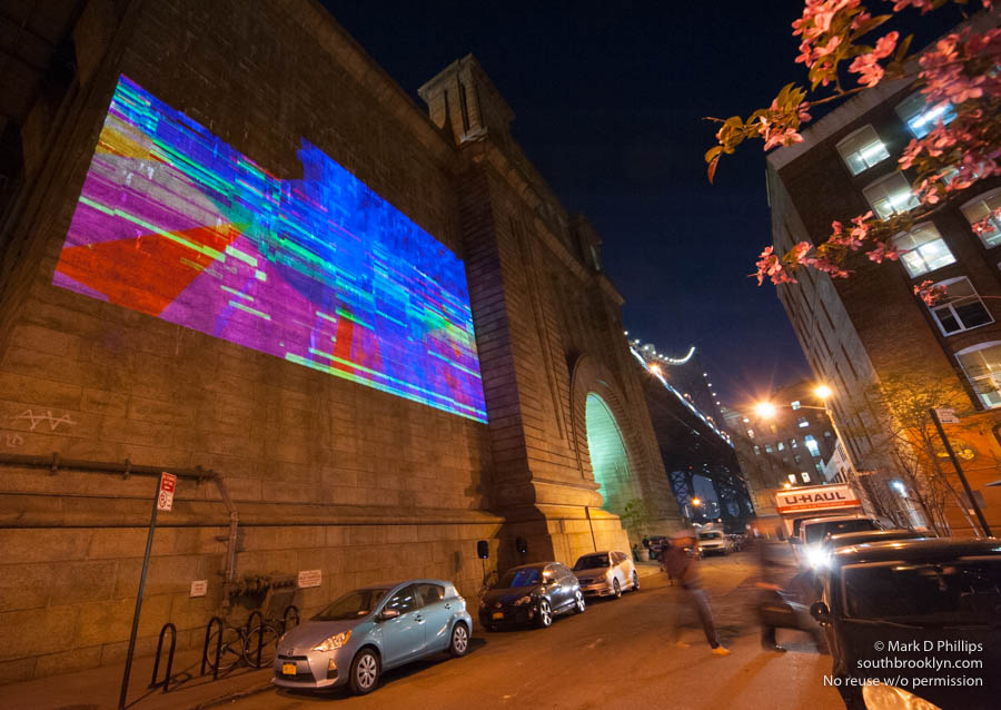 "LIGHT YEAR: In honor of the United Nations' declaration of 2015 as The Year of Light and Light Art, the Manhattan Bridgein DUMBO is coming alive with ""Light Year."" Beginning this May, this year-long series of projected video art will be presented on the First Thursday of every month. ""Submerged!"" provides liquid visions of a multi-layered, every-shifting psychological seascape. Seven video + sound pieces based upon three short stories by co-curator Leo Kuelbs make up the 30 minute looping program presented at the edge of the East River, on the Northern Anchorage of the Manhattan Bridge. A group of visual and sonic-based artists from a variety of countries including Germany, Israel, Italy, USA, Portugal, Brazil and Hungary make ""Submerged!"" a truly international effort. When represented from multiple cultural angles, a mysterious whole reveals itself, always changing, just beneath the viewable surface. ©Mark D Phillips"