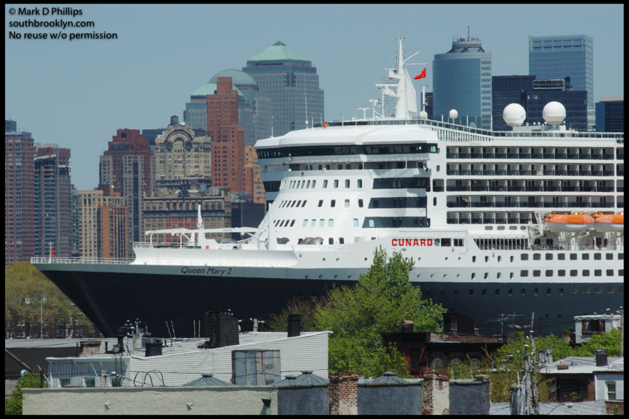 RED HOOK SKYSCRAPER<br><br>Queen Mary 2 looms over the low rooftops of Red Hook in its second visit to the new Brooklyn Cruise Terminal on May 23, 2006. The huge ship joins the New York City skyline as it moors in the narrow area called Buttermilk Channel. ©Mark D Phillips
