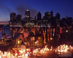 Brooklyn Heights Promenade is covered with candles the nights after the 9/11 attacks as smoke rises from the World Trade Center site in lower Manhattan. ©Mark D Phillips