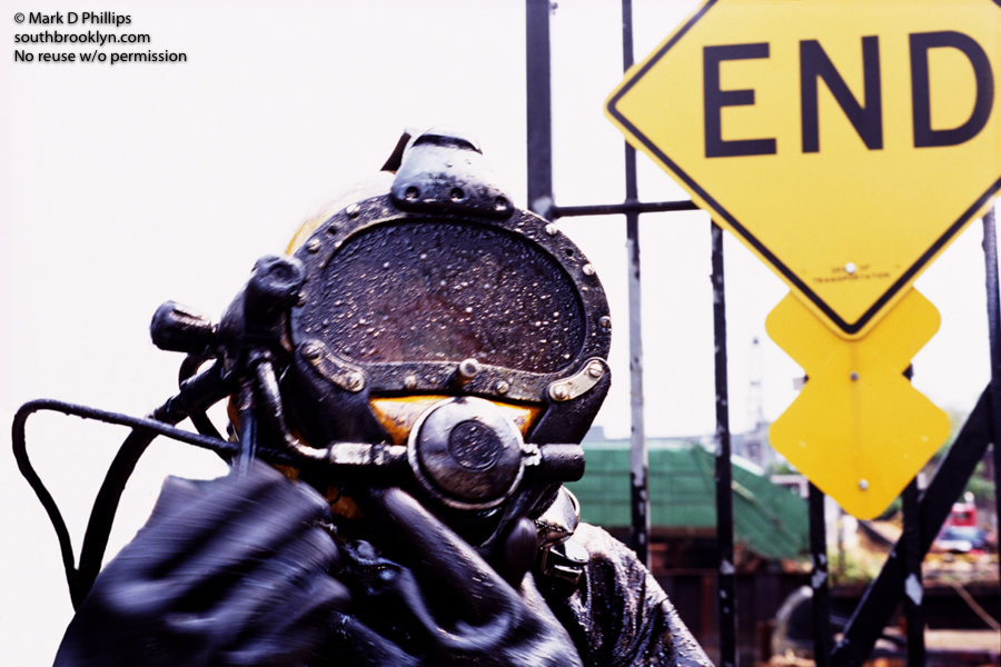 END of DIVE: Diver exits the water covered in black sludge by END sign on Butler Street at the Gowanus Canal in Brooklyn, NY. ©Mark D Phillips