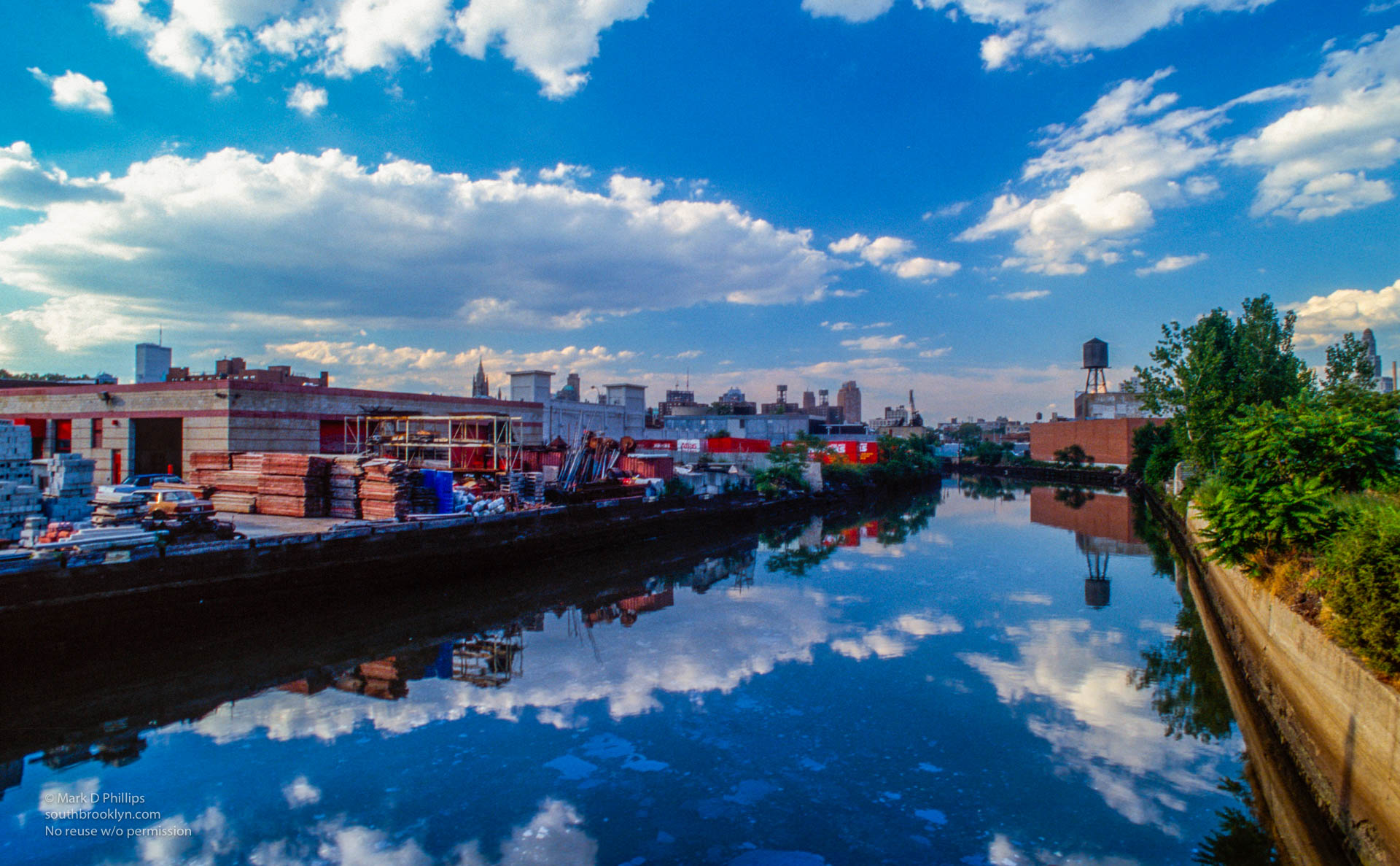 Clouds reflect in the water of the Gowanus Canal looking north with the Twin Towers peeking above the shoreline in 1989. The wall reflected in the water has no graffiti in 1989 and has now joined the past. ©Mark D Phillips
