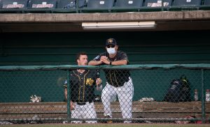 New Britain Bees Manager Ray Guarino wears a mask as a player stands behind in the dugout with the whole first row over the dugout empty during their FCBL game with the Nashua Silver Knights. ©Mark D Phillips