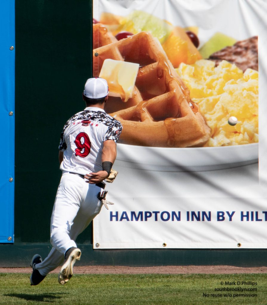 Nashua Silver Knights center fielder Ben Rounds, a sophmore at Harvard, chases the ball into a breakfast photo on a drive to the wall during FCBL game with the North Shore Navigators at Holman Stadium in Nashua, NH. ©Mark D Phillips
