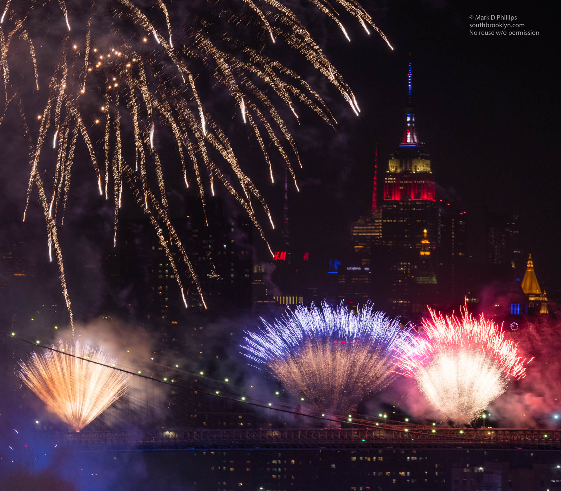 Fans of color burst from the roadway of the Brooklyn Bridge as streamers fall from the sky highlighting the Empire State Building duringThe Macy's 4th of July Fireworks from Brooklyn Bridge Park. ©Mark D Phillips