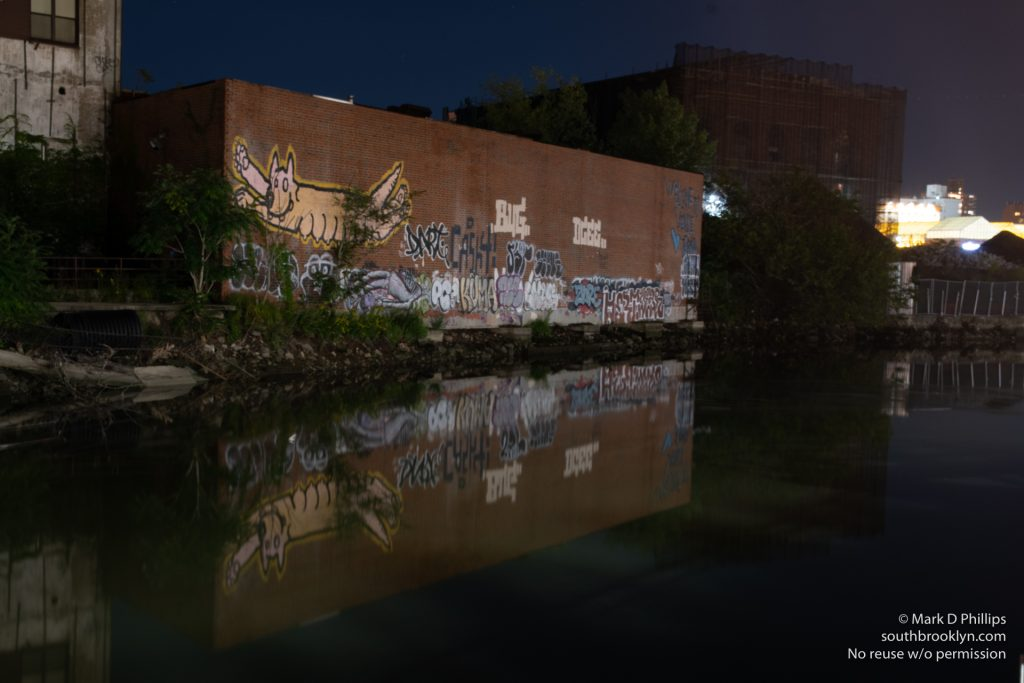 "Since 2016, the patch of graffiti on a warehouse by the Carroll Street Bridge on the bank of the Gowanus Canal welcomed visitors with the tagline 'Welcome to Venice' with the signature ""Love Jerko.\"" But just like the Canal itself, it became a victim of gentrification. The former home of Alex Figliolia Water & Sewer, the 65,000-square-foot industrial building disappeared without a trace. On my first visit to the canal since the pandemic struck, I had one of those \""Oh No\"" moments when I drove across the historic Carroll Street Bridge and realized the graffiti covered wall was gone. Not just gone but obliterated like it had never been there. ©Mark D Phillips"