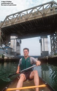 Owen Foote, one of the founders of the Gowanus Dredgers Canoe Club, paddles on the Gowanus Canal with the Ninth Street Subway station looming above in 2000. ©Mark D Phillips