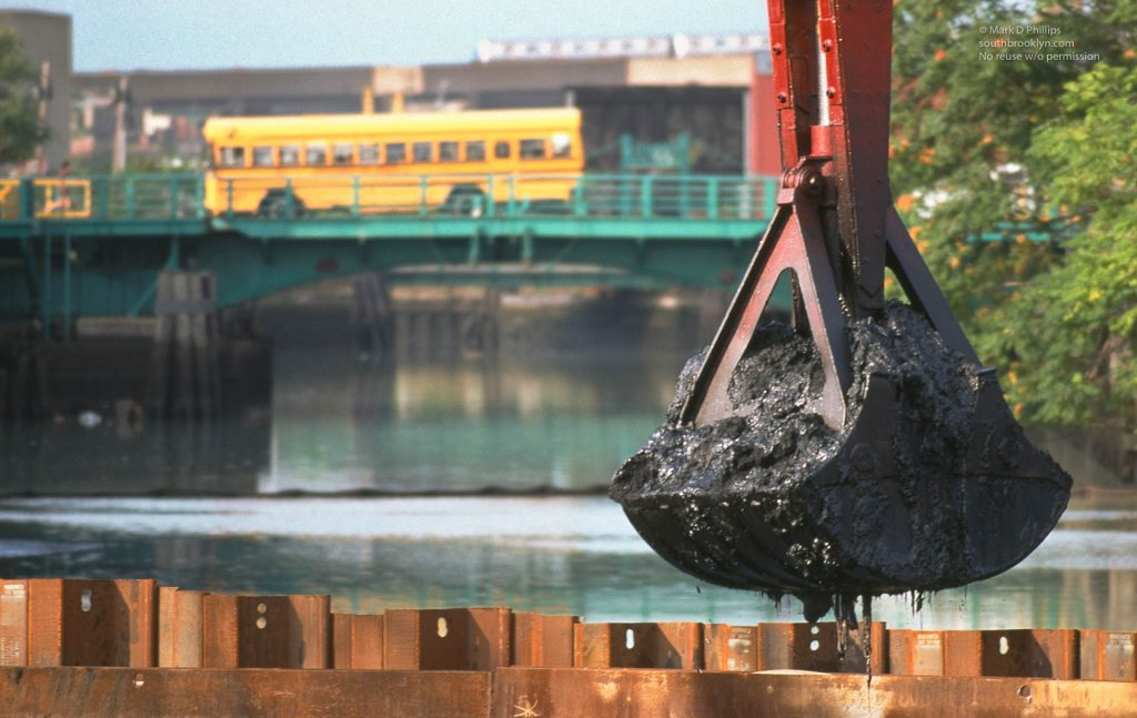 Dredging in the Gowanus Canal in Brooklyn, NY, in 1998 brought up muck laced with environmental toxins as a school bus crosses the Third Avenue Bridge. ©Mark D Phillips