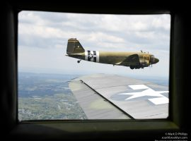Betsy's Biscuit Bomber flies off the wing of Placid Lassie, two of the D-Day Squadron of C47s. ©Mark D Phillips