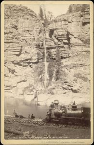 """View of a Denver and Rio Grande Railway excursion train near Chipeta Falls, along the Gunnison River in the Black Canyon of the Gunnison in Gunnison or Montrose County, Colorado. Men stand or sit on locomotive number """"275"""" or beside the tracks. Jackson, William Henry, 1843-1942; [1882-1886?]"""